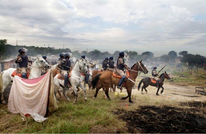Policias antimotines cabalgan luego de desalojar ocupantes de terrenos municipales en Asuncion, Paraguay, 6 de diciembre de 2011. Mas de 400 familias fueron expulsadas. (AP Photo/Jorge Saenz)