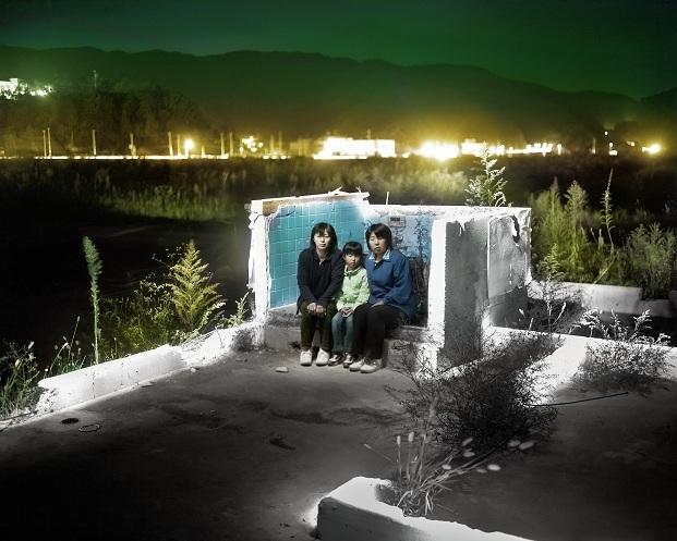 Cimientos. Tomoko Hida, Yoshimi Hida y Sana Hida representan tres generaciones de una misma familia; están sentadas en los restos de lo que fuera el baño de su casa, destruida por el desastre natural que golpeó su país. @Alejandro Chaskielberg